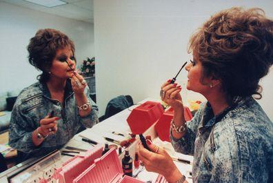 TV talk show host Tammy Faye Bakker Messner applying mascara to eyelashes in mirror in dressing room. (Photo by John Storey/Getty Images)