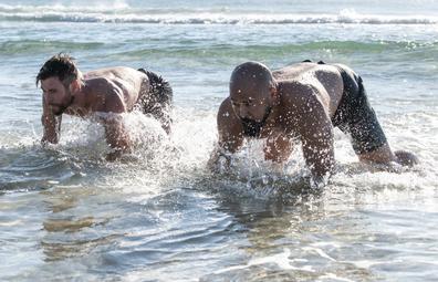 Chris Hemsworth and Centr trainer Da Rulk doing bear crawls in the ocean