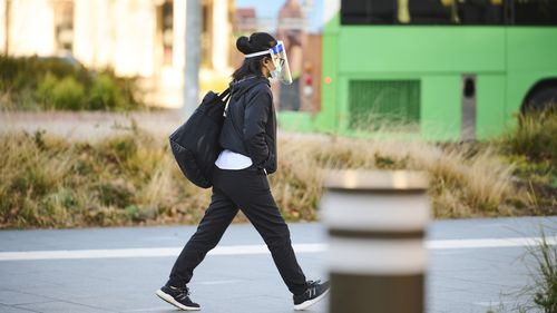 A pedestrian wearing a face shield and mask in Canberra.