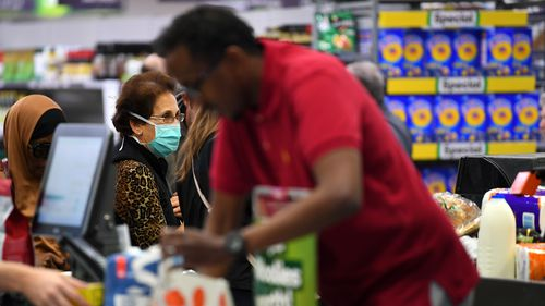 People shopping are seen in Woolworths supermarket in Coburg, Melbourne, Thursday, March 19, 2020.