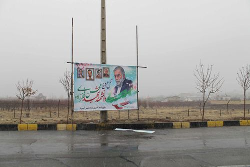 A poster of Mohsen Fakhrizadeh  stands above the spot where he was gunned down outside Tehran.