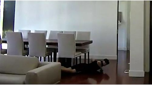 The man can be seen sliding along his stomach on the floor of the Brighton property to avoid being seen (Supplied).
