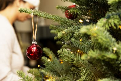 Defocused woman working on hanging ornaments on a tree, with a close up of a tree ornament hanging off the side