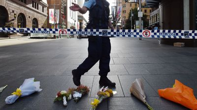 A police officer asks the media and onlookers to move back near flowers laid at the scene. (AAP)