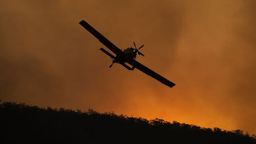 A small aircraft is pictured after dumping fire retardant behind houses at the foot of Mount Tennant as the fire front of the Orroral Valley fire creeps through the Namadgi National Park.