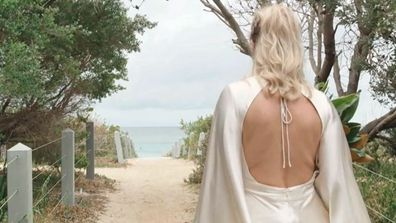 A bride appears to walk on sand with an open-back wedding dress to meet her groom.