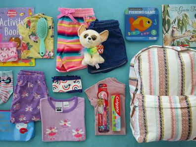 The contents of a care bag, including a backpack, clothes, activity books, hygiene products and more.