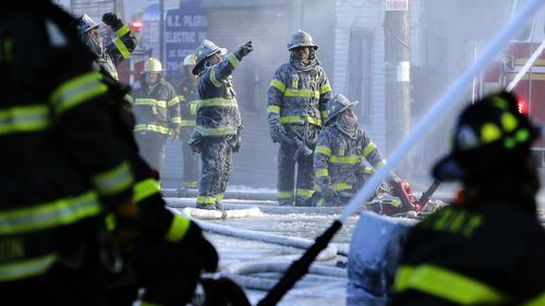 Firefighters in New York are coated in ice as water from their fire engine freezes on their uniforms. (AAP)
