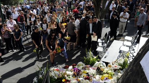 Mourners place flowers during Ms Ban's memorial service. Picture: AAP