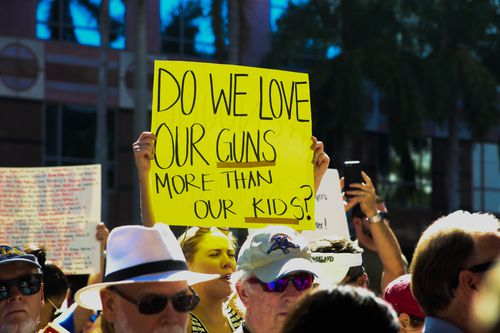 """""""Do we love our guns more than our kids"""", one sign read. (AAP)"""