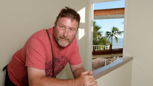 Mick Burrows surveys damage at the rented holiday home. (AAP)