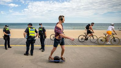 People cycle and skate along St Kilda beach in Melbourne as Victorian Police go on patrol.