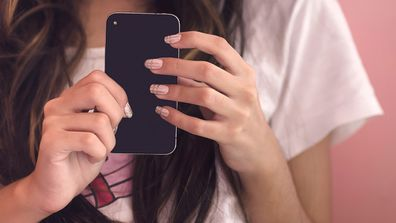 Young woman holding her smart phone, close-up