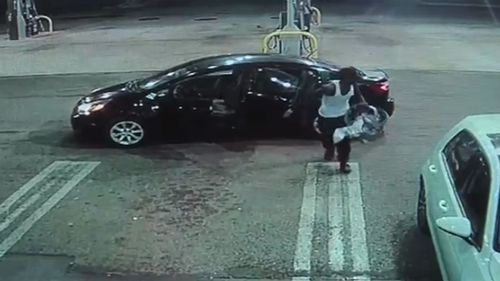 The thief took the baby to the entrance of the petrol station kiosk. The thief was seen struggling to get the baby in the car seat out of the car he'd stolen. Picture:  WPTV