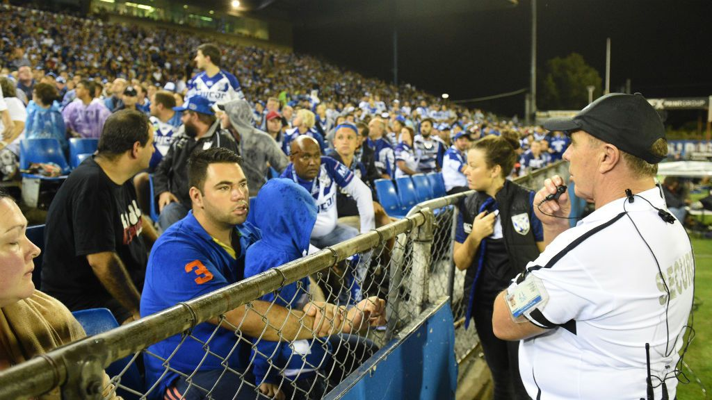 Security guards look towards an area where a bottle was thrown from at Belmore Oval. (AAP)