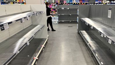Empty shelves of toilet paper are seen at a supermarket in Sydney's CBD.