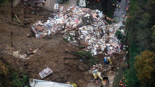 The three-story residential building was hit by the landslide just before 2.30am. (AAP)