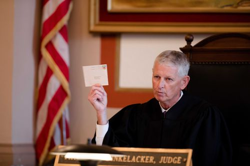 Judge Patrick T. Dinkelacker reads cards he said he received at his home in an apparent effort to intimidate him during an execution of sentence of Former judge Tracie Hunter.