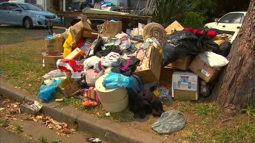 A Sydney hoarder was trapped for over 14 hours when the rubbish inside her home fell on top of her.