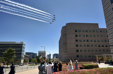 Doctors, nurses and other staff members at the Ronald Reagan UCLA Medical Center watch as the U.S. Air Force Thunderbirds fly over to honor first responders, doctors and nurses in the Westwood section of Los Angeles, Friday, May 15, 2020. (AP Photo/Richard Vogel)