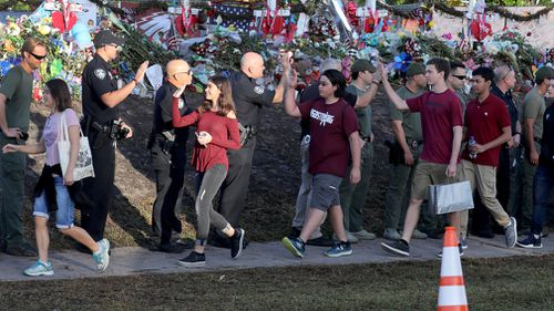 Students are greeted by law enforcement as they head back to school at Marjory Stoneman Douglas High School. (AAP)