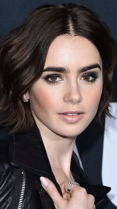 Heavy lashes, smoky silvers and black on Lily Collins.