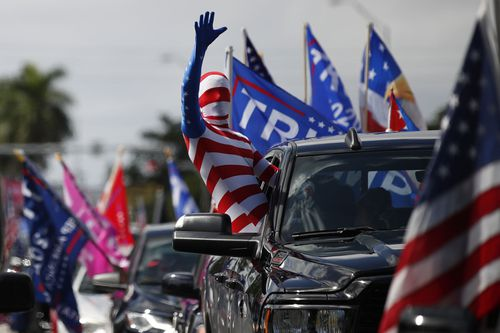 A man wearing a flag-themed body stocking waves from a car as hundreds of vehicles gather at Tropical Park