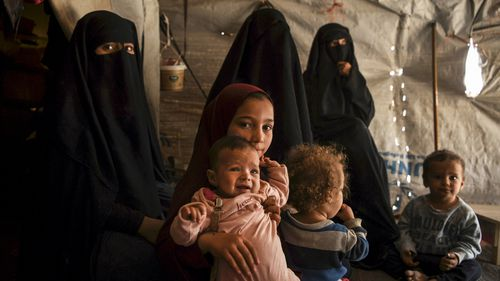 Australian Maysa Assaad, aged nine, holds Shayma Assaad's daughter Mariam in al-Hawl camp.