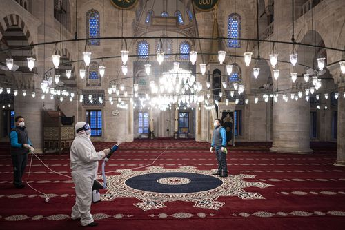 Workers wearing protective clothing disinfect a historical mosque, in Istanbul, Wednesday, March 11, 2020