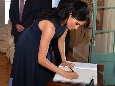 The Duchess of Sussex signing a visitor's book
