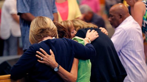 People embrace during a service at the First United Methodist Church in Coral Springs, Florida. (AAP)