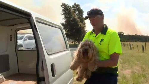 Resident Mark Boswerger places his neighbour's dog in the safety of his vehicle as the fire burns.