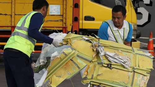 Officials move pieces of wreckage recovered from the crashed Lion Air jet for further investigation.