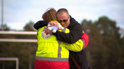 A local man hugs a Red Cross worker at the scene of Ms Dixon's murder. (9NEWS)
