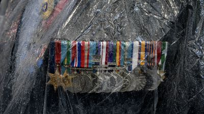 Medals are seen under the plastic raincoat of an ex-serviceman during the Anzac Day march in Sydney. (AAP)