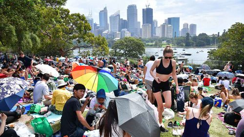 People are seen at Mrs Macquarie's Point in preparation for New Years Eve Fireworks last year.
