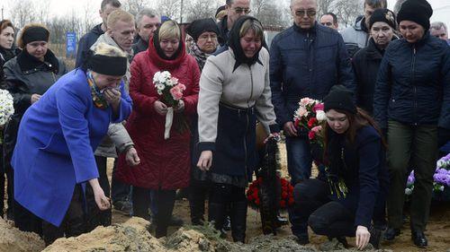 People grieve at the grave of Irina Medyantseva, 50, a victim of the blast at Saint Petersburg metro. (AFP)