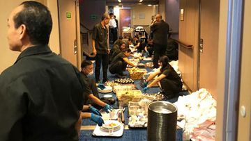 A photo on board the cruise ship Zaandam shows crews packed together while collecting meals.
