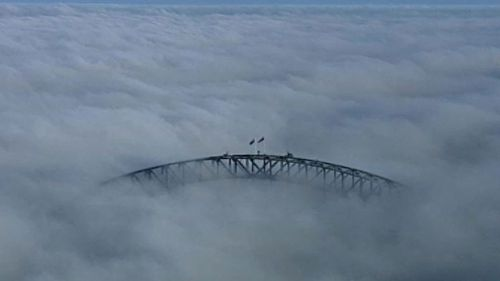 The Sydney Harbour Bridge is just visible above the fog. (9NEWS)