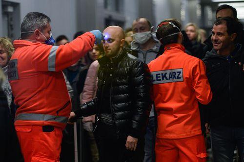 Медицинский работник проверяет температуру пассажира, прибывающего из миланского Бергамо в Краковский международный аэропорт 26 февраля 2020 года.