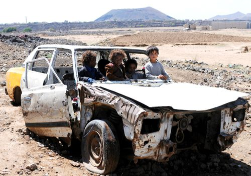 Displaced Yemeni children who with their families fled homes due to the Yemen civil war enjoy riding a damaged car at the outskirts of Sana'a, Yemen. More than three million people fled their homes since the war erupted on March 2015. (Getty)