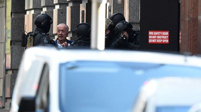 A released hostage speaks with police on Phillip Street in the central business district of Sydney. (AAP)