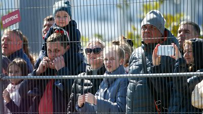Crowds gather outside the fence