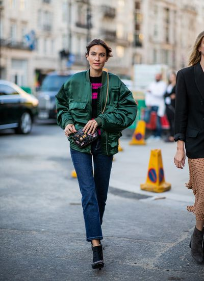 Alexa Chung wearing green bomber jacket, cropped denim jeans seen outside Simone Rocha during London Fashion Week.