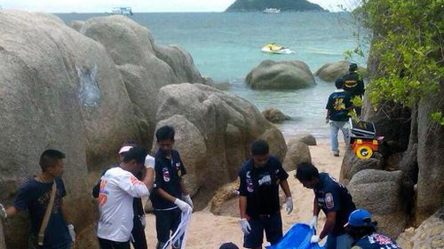 Thai rescue workers wrap the bodies of two British tourists who were found dead on a beach of Koh Tao island, Surat Thani province, southern Thailand. (AAP)