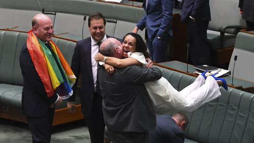 Liberal MP Warren Entsch lifts up Labor MP Linda Burney as they celebrate the passing of the Marriage Amendment Bill in the House of Representatives at Parliament House in Canberra, Thursday, December 7, 2017.