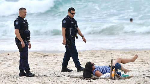 Queensland Police are seen moving on a sunbather from the beach at Burleigh Heads on April 10.