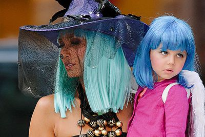 Cookbook celeb Padma Lakshmi wears a green wig and witch's hat as she clutches daughter Krishna in an angel-winged Halloween costume in New York City.