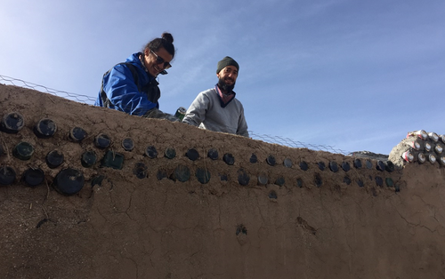 Derrick, left, and Mario, right, from Puerto Rico, learn how to build an Earthship. (9NEWS)