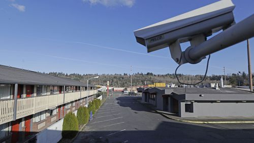 In this March 4, 2020 file photo, a security camera is shown on the second floor of a row of rooms at a motel in Kent, Wash. Hackers aiming to call attention to the dangers of mass surveillance said they were able to peer into hospitals, schools, factories, jails and corporate offices after they broke into the systems of a security-camera startup